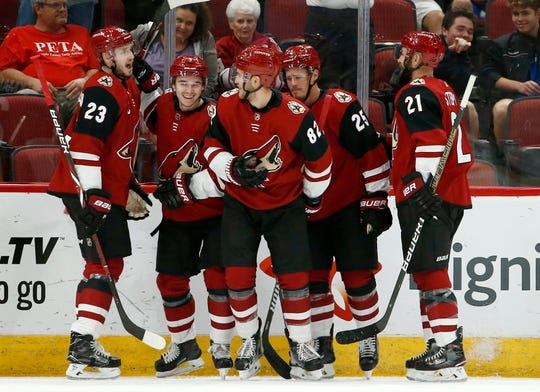 Arizona Coyotes defenseman Jordan Oesterle (82) celebrates his goal against the Anaheim Ducks with Oliver Ekman-Larsson (23), Clayton Keller, second from left, Nick Cousins (25) and Derek Stepan (21) during the first period of an NHL preseason hockey game, Saturday, Sept. 22, 2018, in Glendale, Ariz.