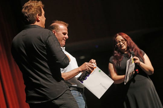 Chandler Mayor Jay Tibshraeny opens the envelope containing Mike Super's headline prediction at Chandler Center for the Arts on Sept. 22, 2018, with The Arizona Republic's Lita Beck. Super mailed his prediction to the city of Chandler a month before the show.