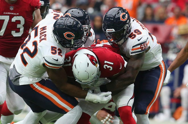 Chicago Bears linebacker Khalil Mack (52) makes a tackle on Arizona Cardinals running back David Johnson (31) with help from Danny Trevathan (59) during the first half of an NFL football game, Sunday, Sept. 23, 2018, in Glendale, Ariz. (AP Photo/Ralph Freso)
