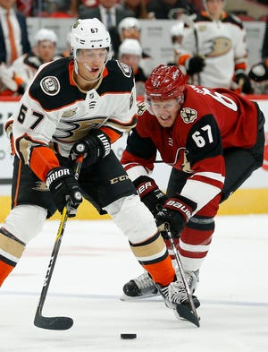 Anaheim Ducks center Rickard Rakell, left, battles with Arizona Coyotes left wing Lawson Crouse, right, for the puck during the first period of an NHL preseason hockey game Saturday, Sept. 22, 2018, in Glendale, Ariz. (AP Photo/Ross D. Franklin)