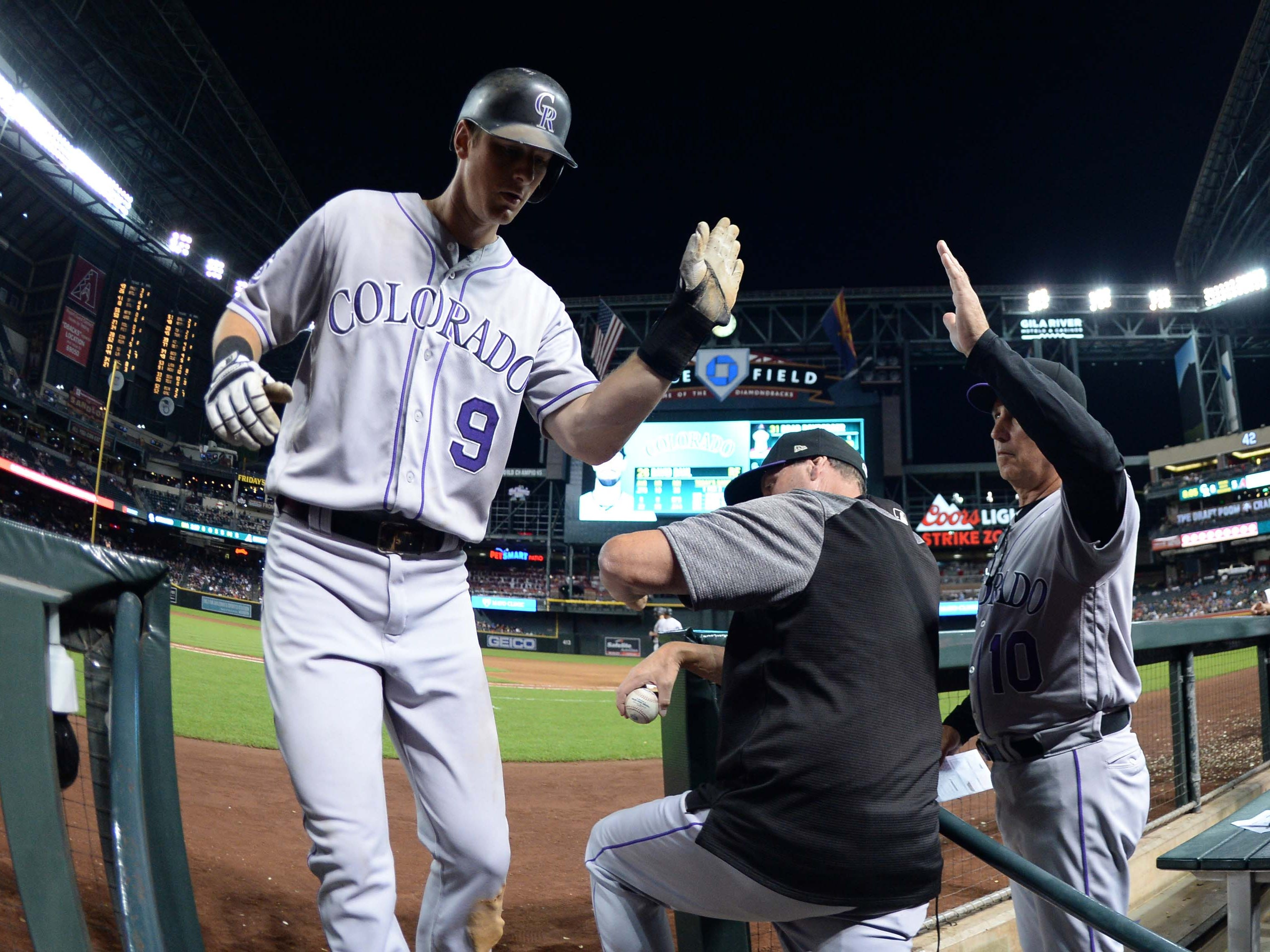 Sep 22, 2018; Phoenix, AZ, USA; Colorado Rockies second baseman DJ LeMahieu (9) slaps hands with Colorado Rockies manager Bud Black (10) after scoring a run against the Arizona Diamondbacks during the ninth inning at Chase Field.