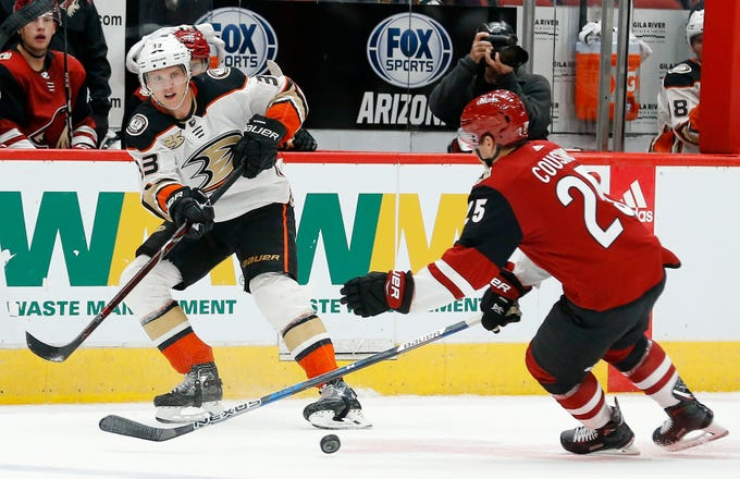 Anaheim Ducks right wing Jakob Silfverberg (33) passes the puck under the stick of Arizona Coyotes center Nick Cousins (25) during the third period of an NHL preseason hockey game Saturday, Sept. 22, 2018, in Glendale, Ariz. The Coyotes defeated the Ducks 6-1.