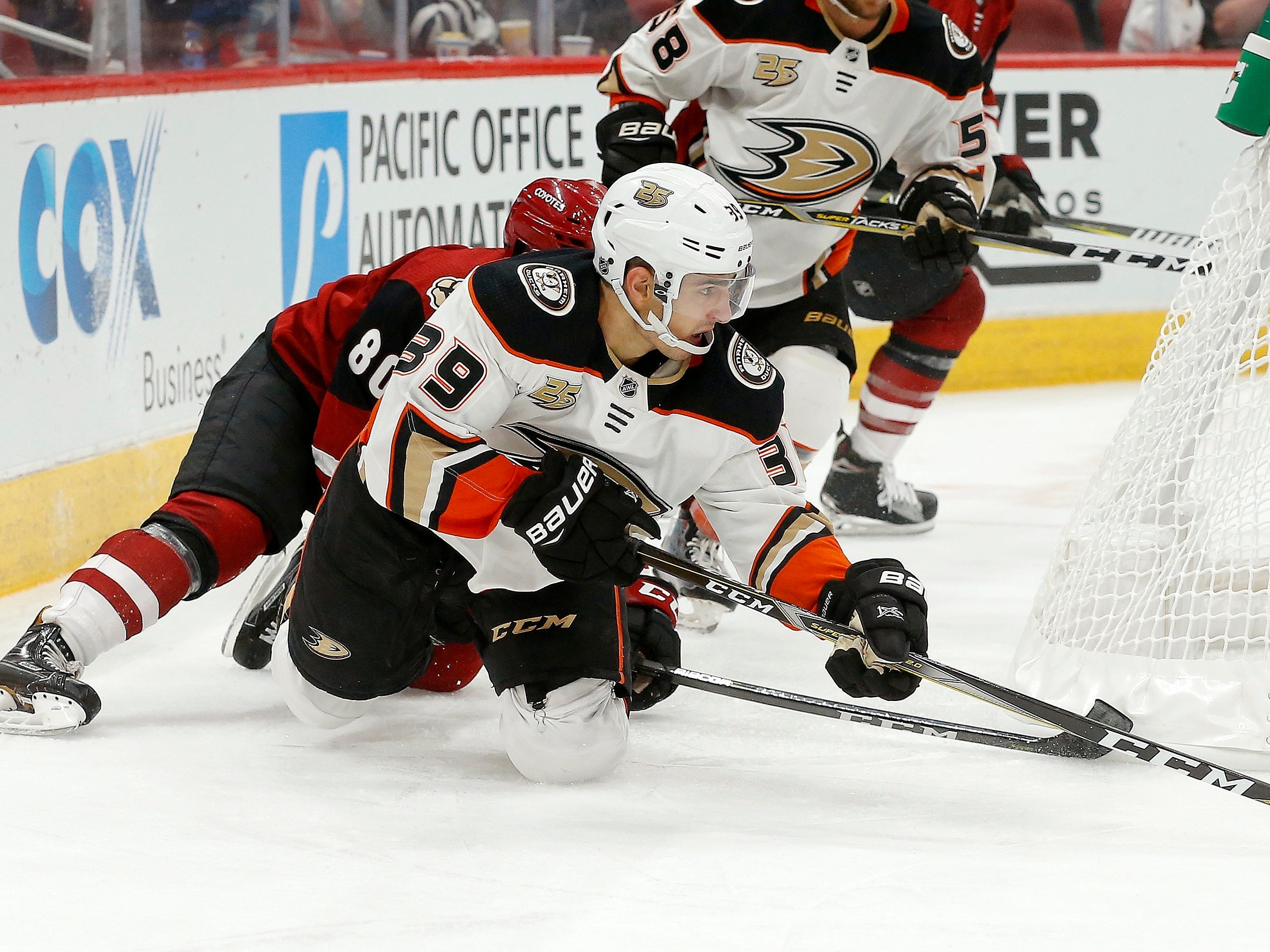 Anaheim Ducks center Joseph Blandisi (39) gets tripped up by Arizona Coyotes left wing Brayden Burke (80) during the third period of an NHL preseason hockey game Saturday, Sept. 22, 2018, in Glendale, Ariz. The Coyotes defeated the Ducks 6-1.