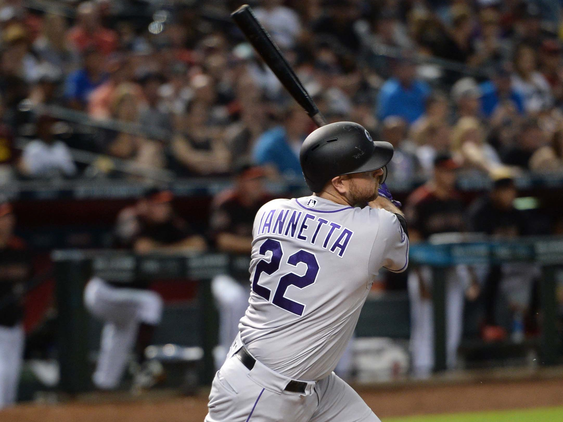 Sep 22, 2018; Phoenix, AZ, USA; Colorado Rockies catcher Chris Iannetta (22) hits a two RBI single against the Arizona Diamondbacks during the third inning at Chase Field.