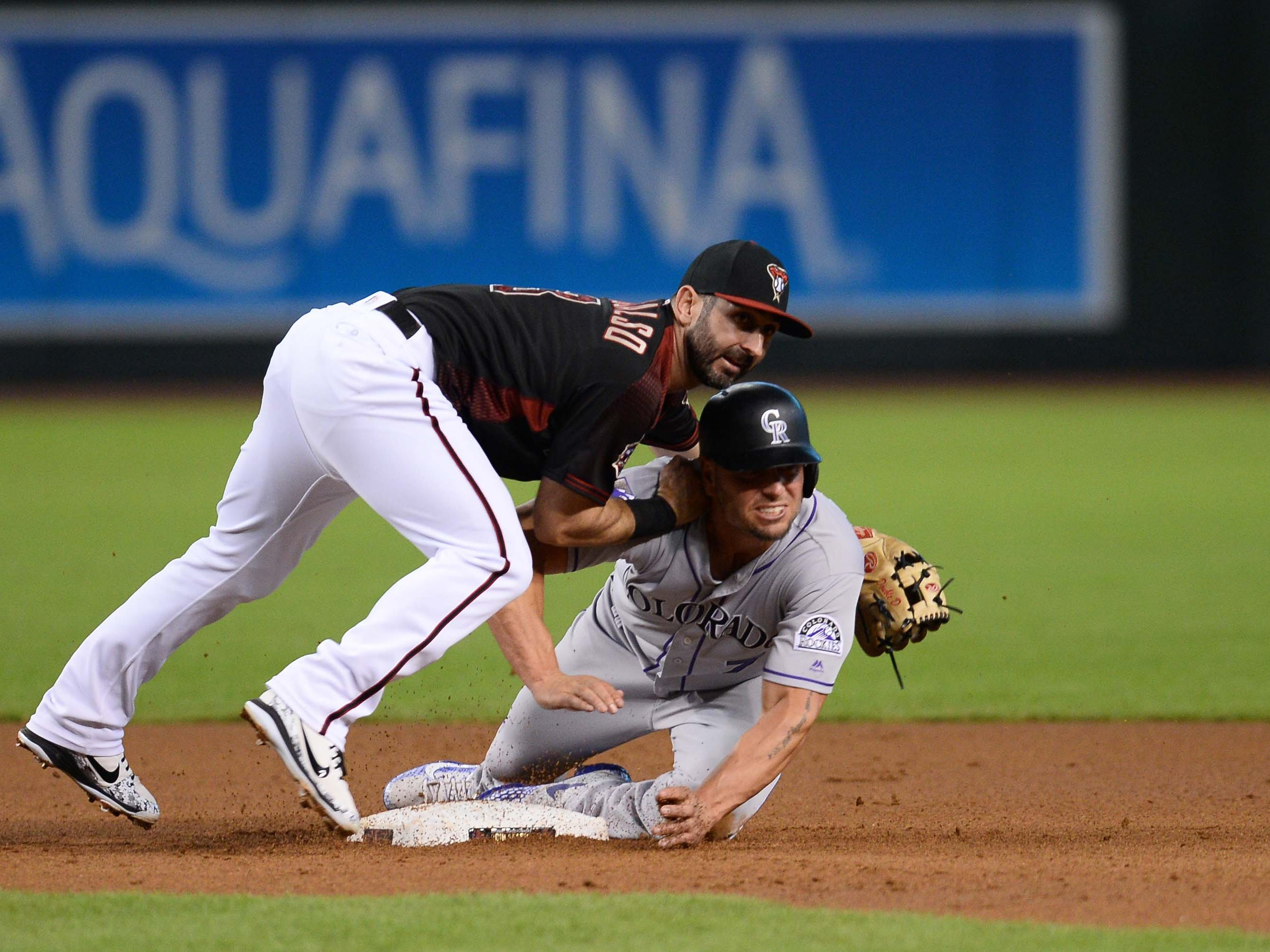 Sep 22, 2018; Phoenix, AZ, USA; Arizona Diamondbacks third baseman Daniel Descalso (3) and Colorado Rockies left fielder Matt Holliday (7) look as Descalso completes a double play during the first inning at Chase Field.