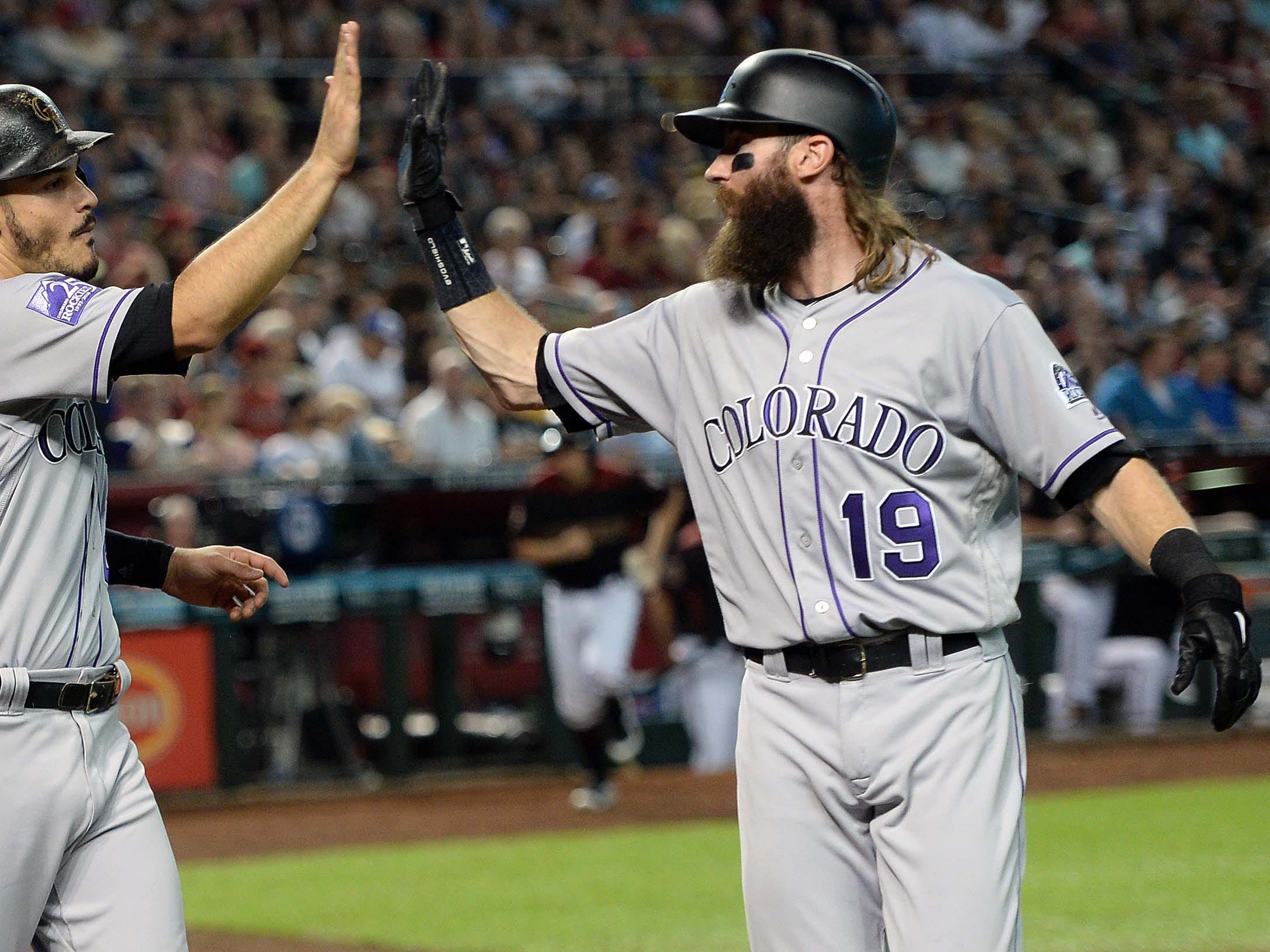Sep 22, 2018; Phoenix, AZ, USA; Colorado Rockies third baseman Nolan Arenado (28) and Colorado Rockies center fielder Charlie Blackmon (19) high five after scoring runs against the Arizona Diamondbacks during the third inning at Chase Field.