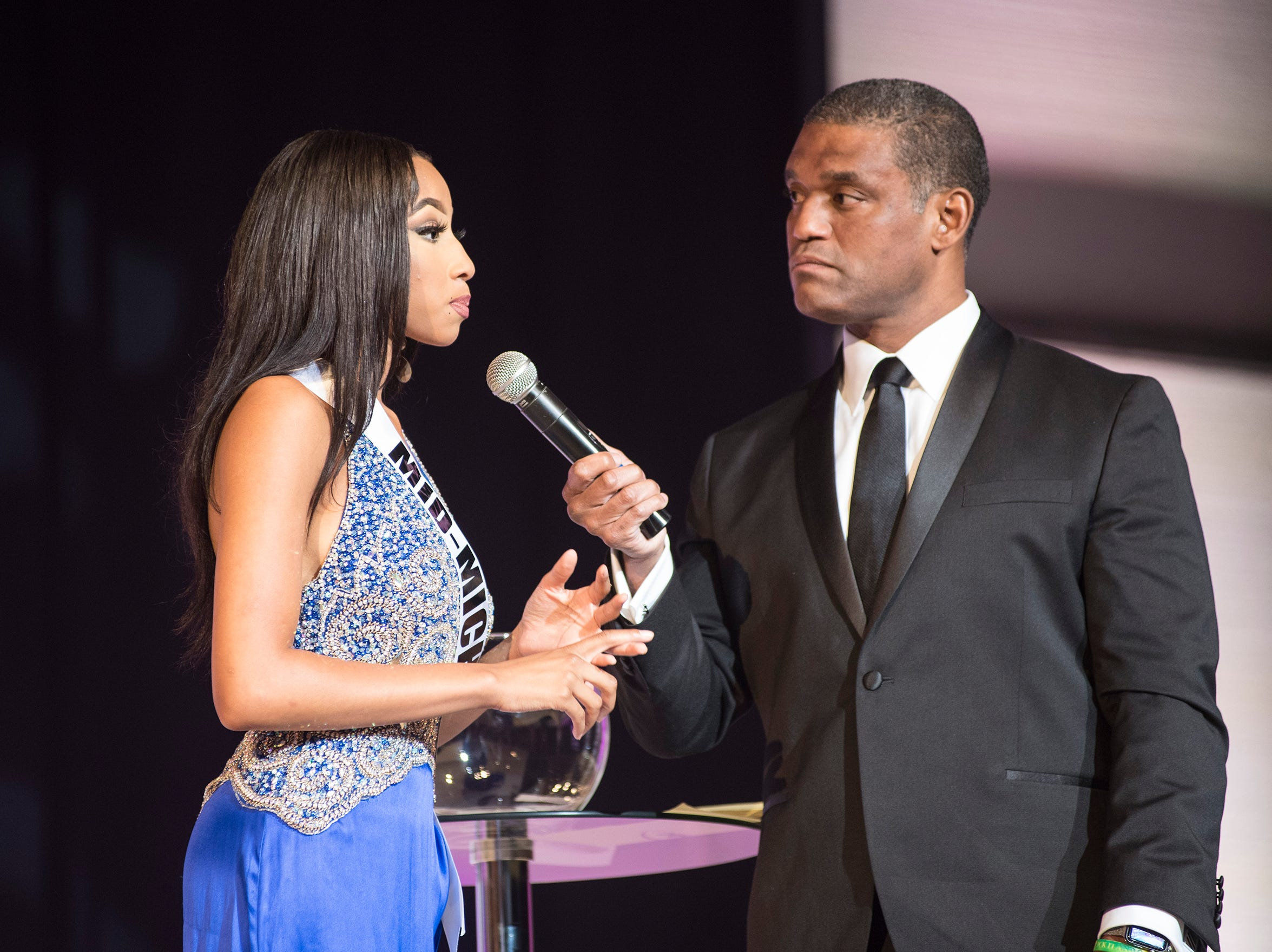 Miss Mid-Michigan Unjanee' Wells, left, is questioned by Cincinnati TV personality Rob Williams Saturday, Sept. 22, 2018 during the final round of the Miss Michigan USA pageant at McMorran Theater.