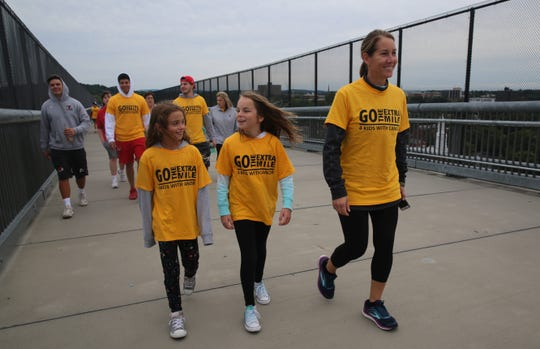 Elna Stanford (right), the wife of the Marist women's rowing team head coach, walks with her daughter, Charlotte Sanford (middle), and her daughter's friend, Grace Schramm (left), during Morgan's Walk on Sunday. They said they were happy to be raising awareness about childhood cancer.