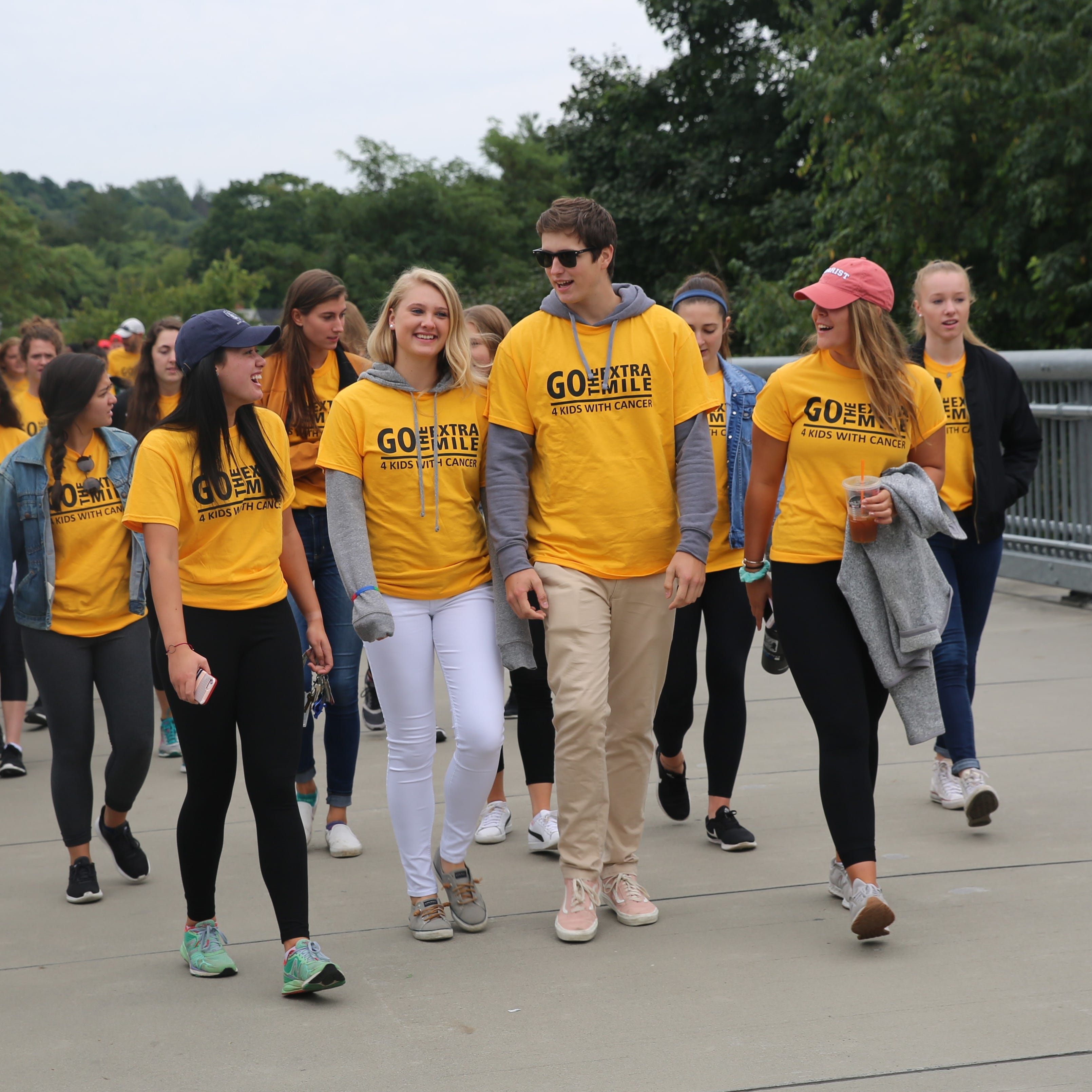 Marist students (from left to right) Kaela Brunetti, Morgan Zuch, her boyfriend, Tom Nalis, and Sara Barker lead the hundreds participating in the inaugural Morgan's Mile walk. Morgan, a childhood cancer survivor, volunteers at The Morgan Center the preschool for kids with cancer that her mother started in her honor.