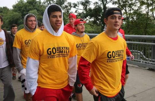 Avery Nesmith (left) and Alex Viola (right), both members of the Marist men's lacrosse team, walk alongside their teammates on Sunday during the inaugural Morgan's Mile walk. They said they have participated in community events in the past.