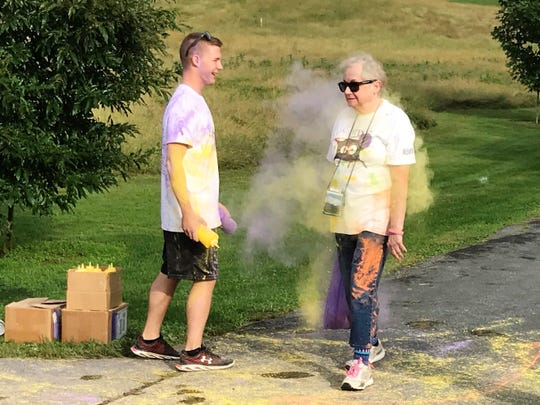 Christopher Sanbower, Chambersburg, douses Joann Johnson, with purple and yellow cornstarch on Saturday, Sept. 22, 2018, at the third annual ITP Matters Color Run at Norlo Park, Fayetteville. Johnson has ITP, a rare blood disorder.