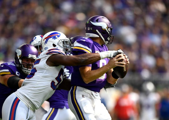 Jerry Hughes #55 of the Buffalo Bills strips the ball out of the hands of Kirk Cousins #8 of the Minnesota Vikings in the first quarter of the game at U.S. Bank Stadium on September 23, 2018 in Minneapolis, Minnesota.