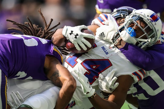 Buffalo Bills wide receiver Ray-Ray McCloud III (14) is tackled by Minnesota Vikings cornerback Mackensie Alexander (20) and cornerback Trae Waynes (26) during the first quarter.