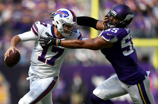 Josh Allen (17) of the Buffalo Bills runs with the ball and stiff-arms defender Anthony Barr (55) of the Minnesota Vikings in the first half of the game at U.S. Bank Stadium on Sept. 23, 2018 in Minneapolis. Barr was penalized on the play for a horse-collar tackle.