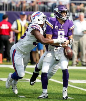 """Minnesota Vikings quarterback Kirk Cousins fumbles as he is hit by Buffalo Bills defensive end Jerry Hughes, who is fearful of getting flagged for roughing-the-passer with NFL emphasizing protection of quarterbacks. """"It's making the game soft and to be completely honest, I'm scared as hell,'' he said."""