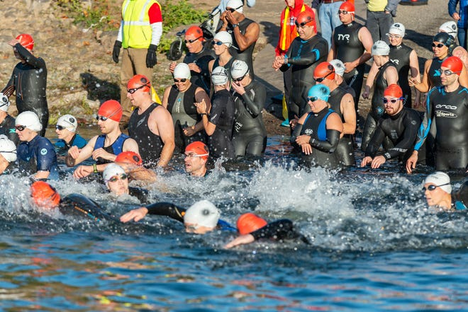 Triathletes dive into the brisk Willamette River to start the race.