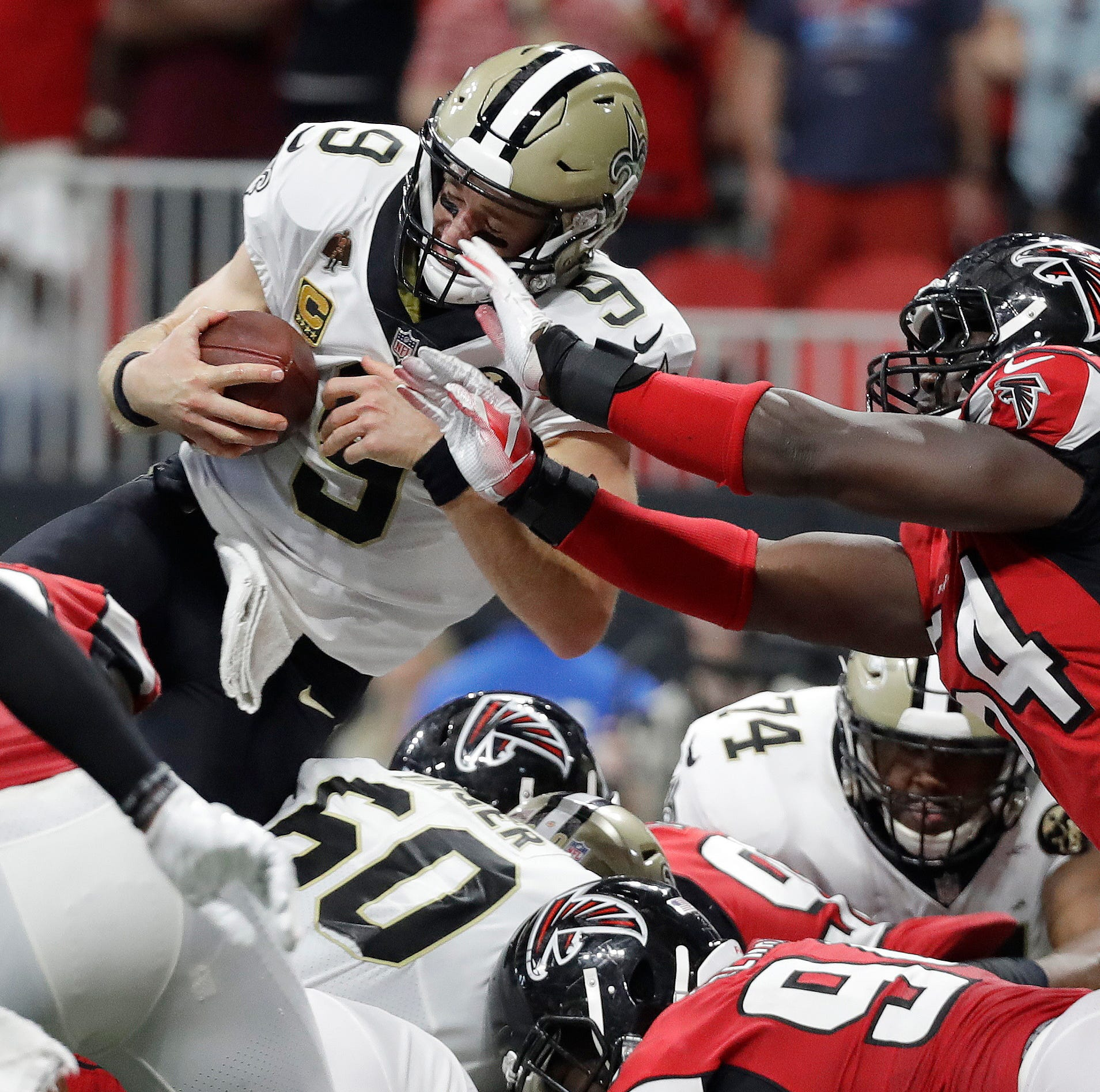 New Orleans Saints quarterback Drew Brees (9) leaps over the goal line for a touchdown against the Atlanta Falcons during overtime of Sunday's game. New Orleans won, 43-37.