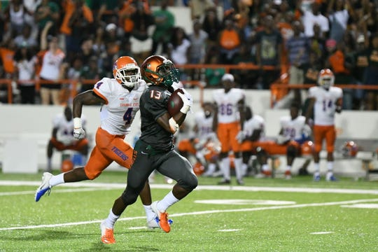 Bishop Bonnett runs by Savannah State defensive back John Wilson. His two touchdowns helped the Rattlers to a 31-13 win.