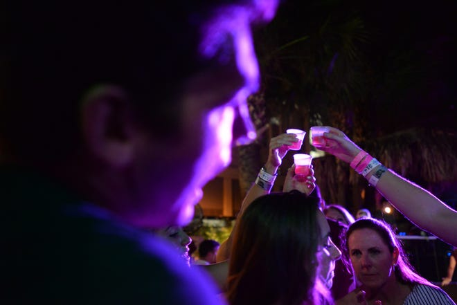 Patrons hold up shots in a toast at Potbelly's Bar in Tallahassee, Fla. Saturday, Sept. 22, 2018.