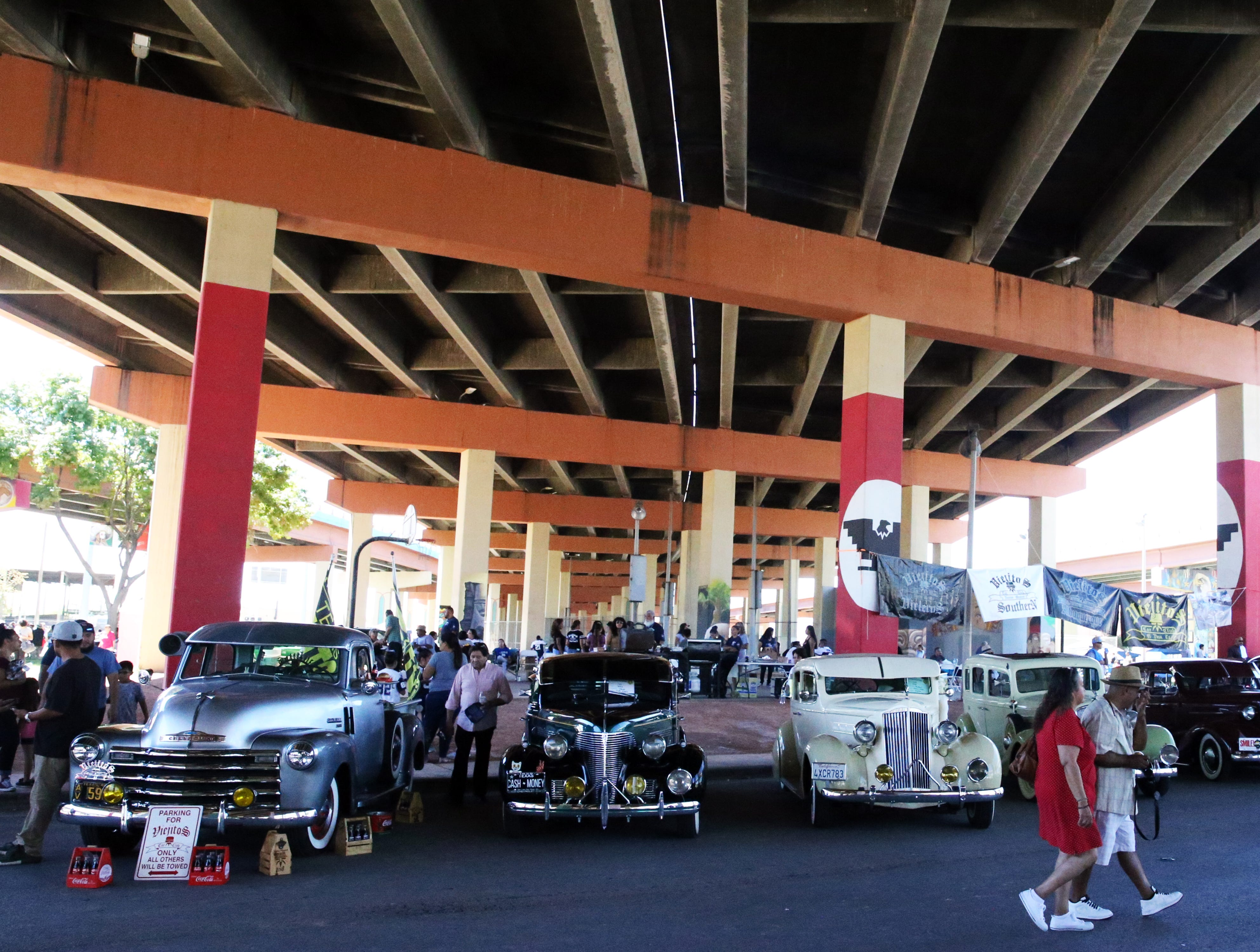 """Classic cars line Durazno Ave. below the overpasses at Lincoln Park during the 14th Annual Lincoln Park Day car show Sunday. Hector Gonzalez of the Lincoln Park Conservation Committee said over 200 cars and motorcycles registered for the event and expected to see between 4 and 5 thousand people attend. The event celebrates the Mexican-American, Chicano and Indigenous culture, its history and traditions, Gonzalez said. El Paso car clubs were joined by clubs from Los Angeles, San Diego, Phoenix, Albuquerque, Oklahoma City, San Antonio and other places. Several Matachines groups paraded around the park. Chris Melendez of Odessa, TX brought along his customized 3-time Lowrider Magazine World Champion """"Bomb of the Year"""" 1951 Chevy Deluxe called 'Blvd. Bully.' People crowded around the car to view its intricate paint work and heavily chromed engine and other components. The event was free to the public. Car registration proceeds go back to the park to fund events like the car show, create murals and for other expenses, Gonzalez said."""
