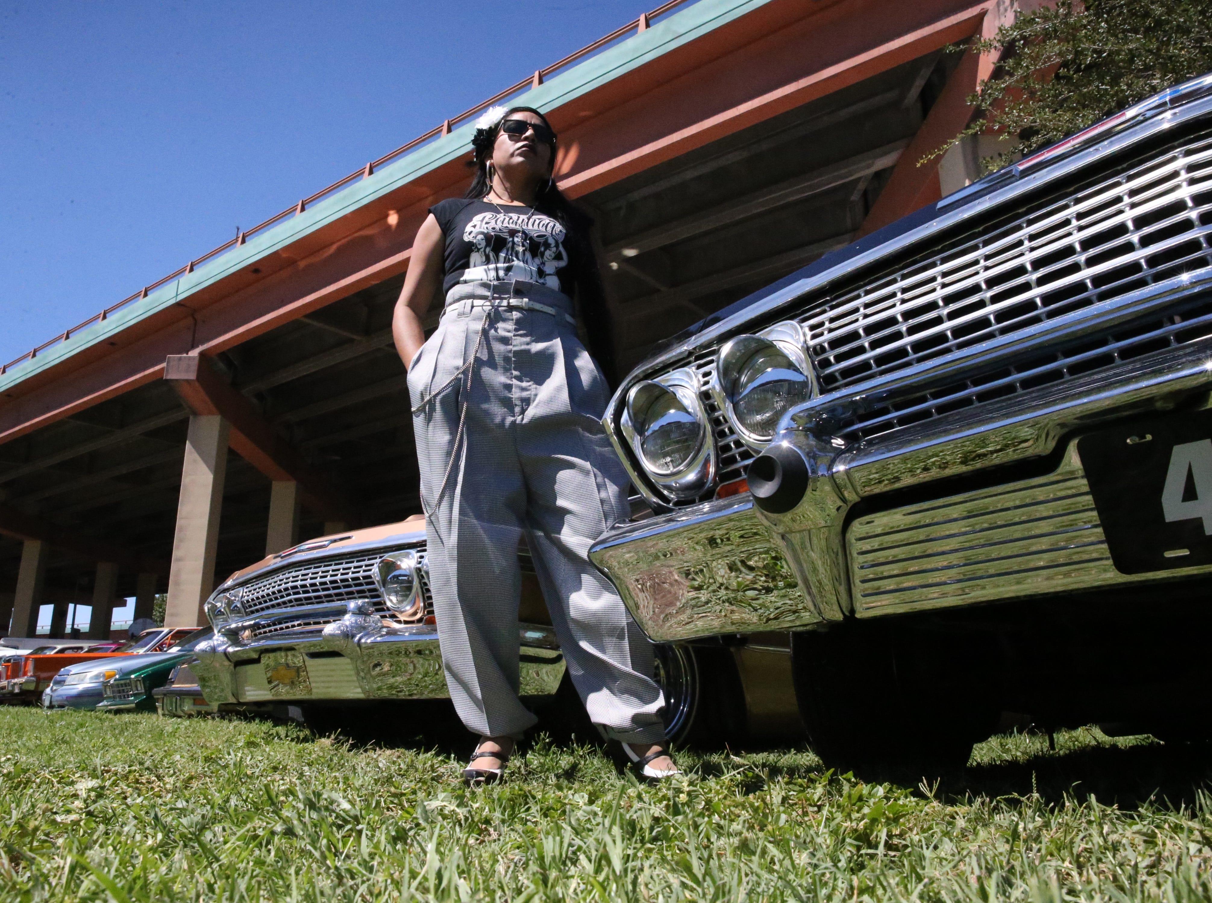 Griselda Palacios of Juarez poses by lowriders in Pachuca style Saturday.