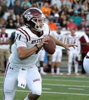 NMSU quarterback Josh Adkins scrambles while looking for a receiver downfield Saturday against UTEP.