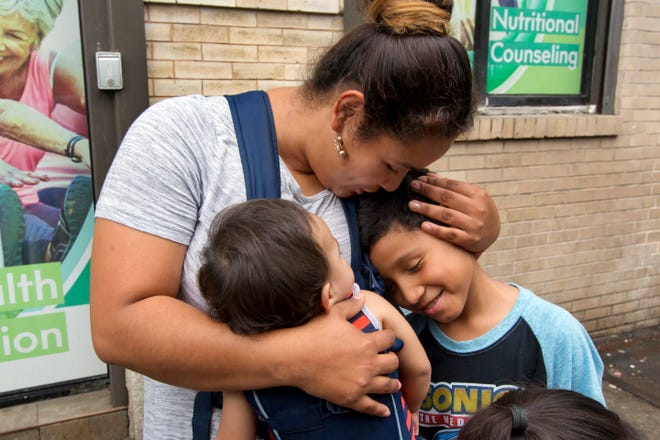 In this Aug. 3 photo, Honduran Eilyn Carbajal hugs her then-8-year-old son Nahun Eduardo Puerto Pineda, right, after they were reunited at the Cayuga Center in New York. Fearful immigrant families hoping to reunite with children and teenagers who crossed the border alone are facing an intimidating system that includes submitting fingerprints by all adults in the household where a migrant child will live. Under new rules, the fingerprints are shared with Immigration and Customs Enforcement.
