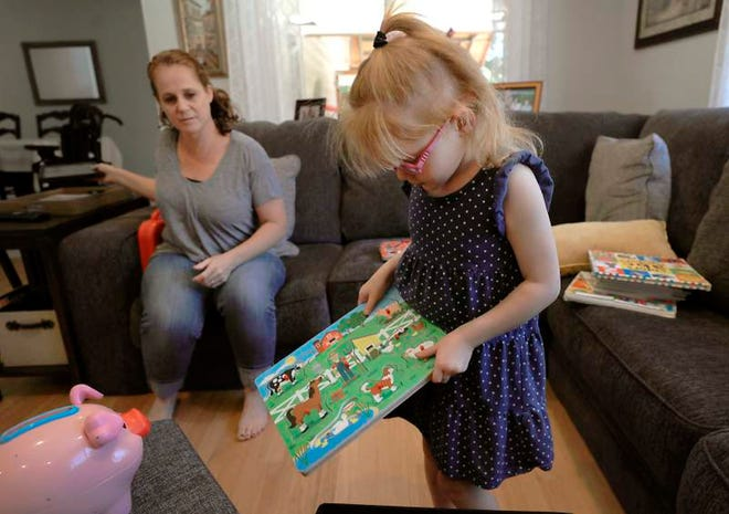 In this July 23 photo taken minutes before having a seizure, Brooke Adams plays with her toys with her mother, Jana, at their home in Santa Rosa. A judge says the California kindergartner can keep bringing a cannabis-based drug used for emergency treatment of a rare form of epilepsy to her public school.
