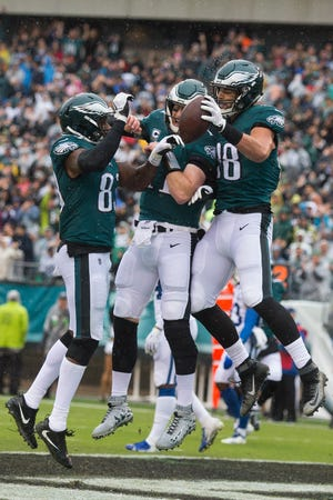 Eagles' Carson Wentz, center, Josh Perkins, Left, and Dallas Goedert celebrate a touchdown Sunday at Lincoln Financial Field.
