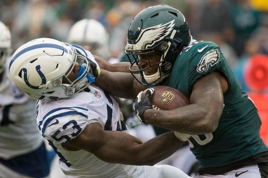Eagles' running back Corey Clement (30) fights past the Colts' Darius Leonard (53) Sunday at Lincoln Financial Field. The Eagles defeated the Colts 20-16.
