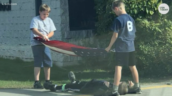 The photo shows three fifth graders working together to take down their flag at school. Struggling to keep the flag off the ground, one of the boys laid on the ground to protect it.