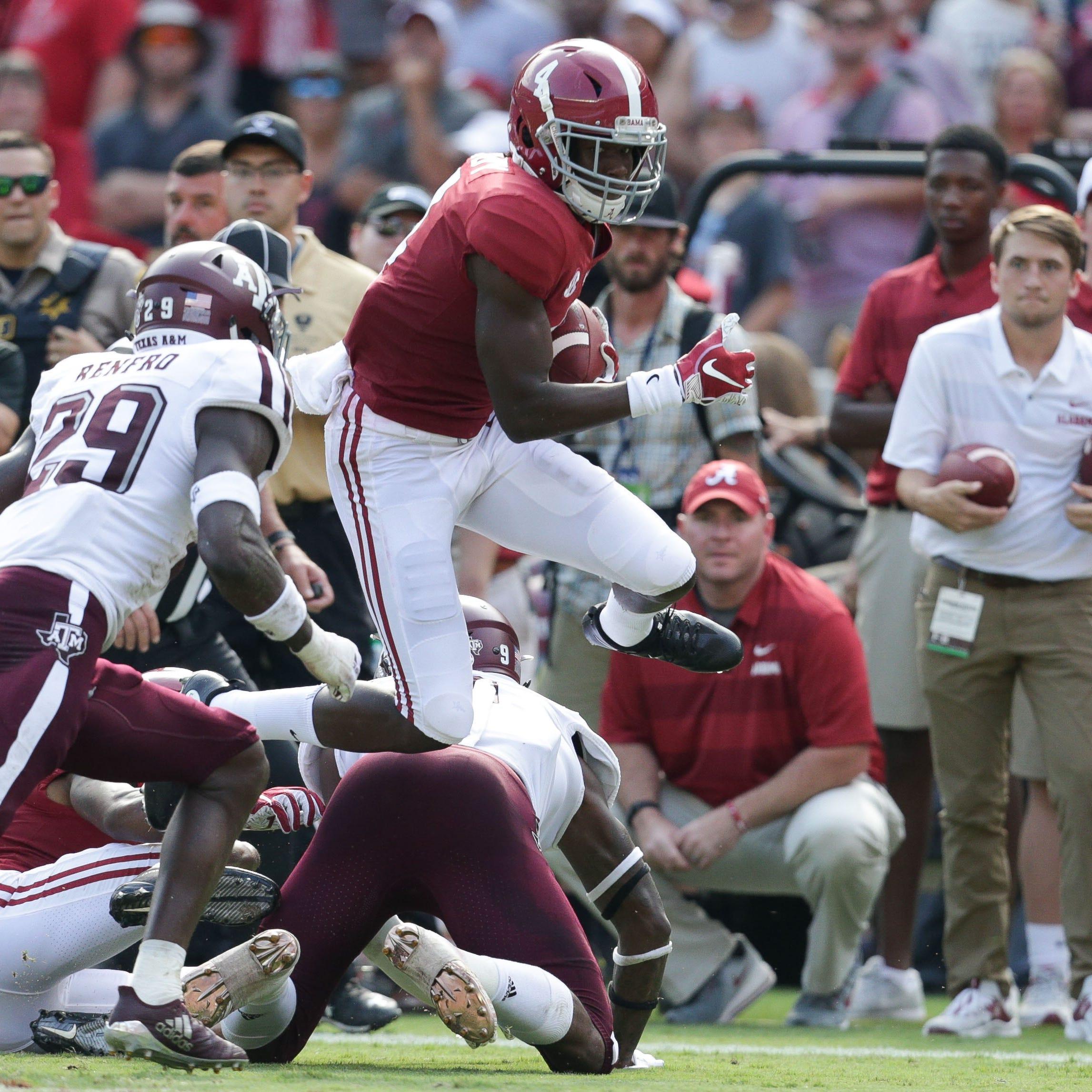 Alabama wide receiver Jerry Jeudy leaps past a...