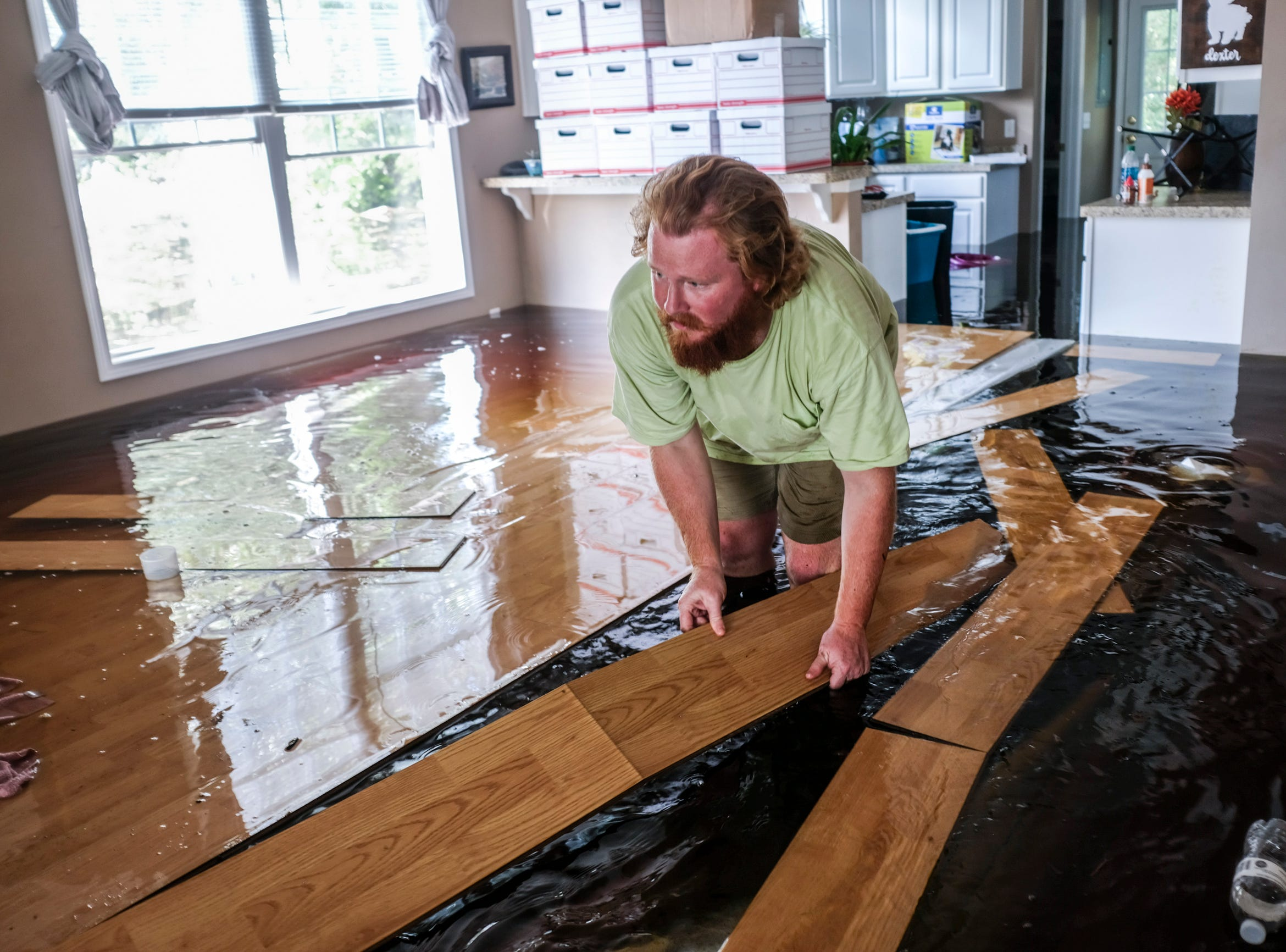 David Covington moves floating floor boards out of his path inside his flooded Conway, S.C. home on Sunday, Sept. 23, 2018.