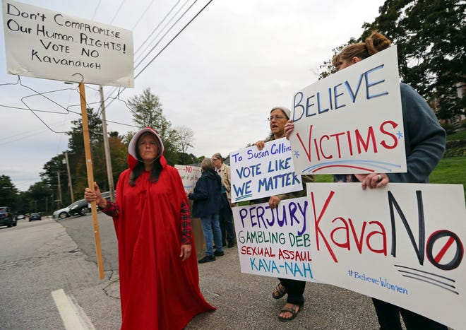 Demonstrators hold signs outside Saint Anselm College, Sept. 21, 2018, in Manchester, New Hampshire.