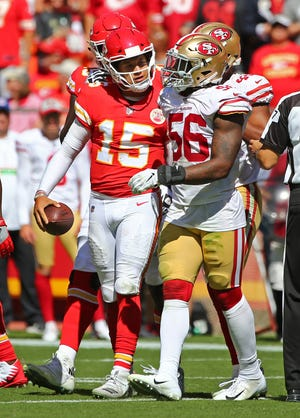 Kansas City Chiefs quarterback Patrick Mahomes (15) talks to San Francisco 49ers linebacker Reuben Foster (56) after a late hit in the first half at Arrowhead Stadium.
