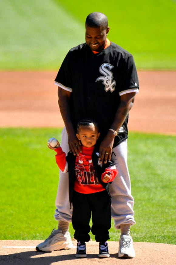 Kanye West and his son, Saint, throw out a ceremonial first pitch before the game between the Chicago White Sox and the Chicago Cubs at Guaranteed Rate Field.