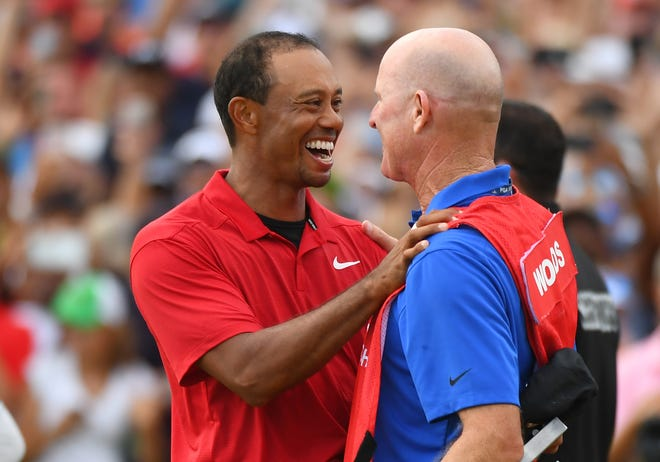 Tiger Woods celebrates with caddie Joe LaCava after winning the Tour Championship.
