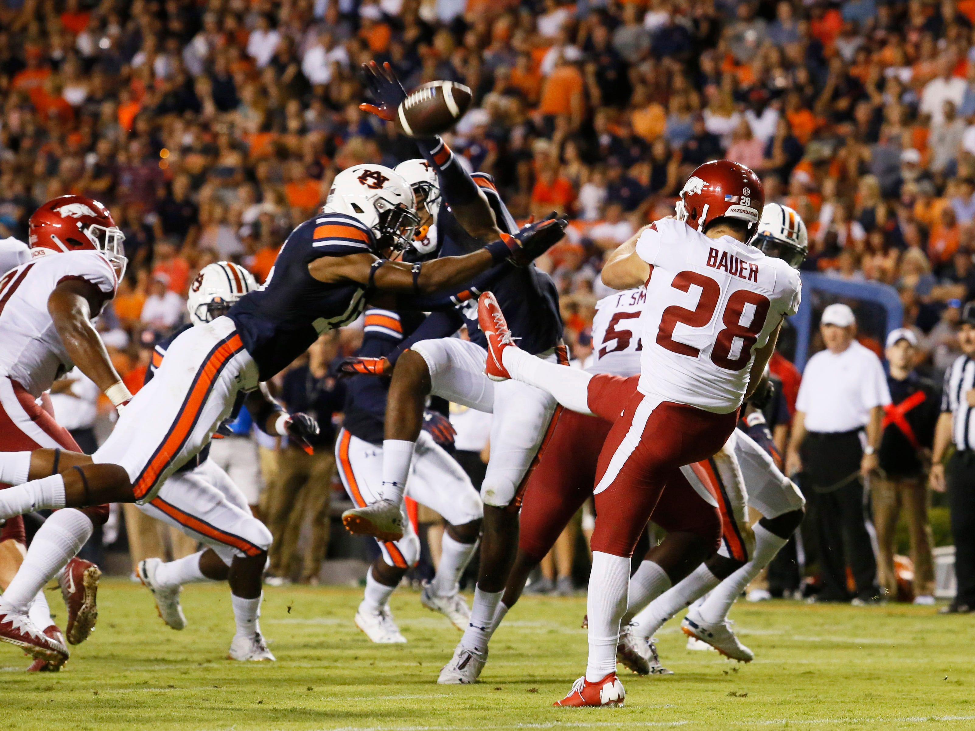 Arkansas Razorbacks punter Reid Bauer (28) has his punt blocked by Auburn Tigers Jordyn Peters (15) and Jamien Sherwood (9) during the second quarter at Jordan-Hare Stadium.