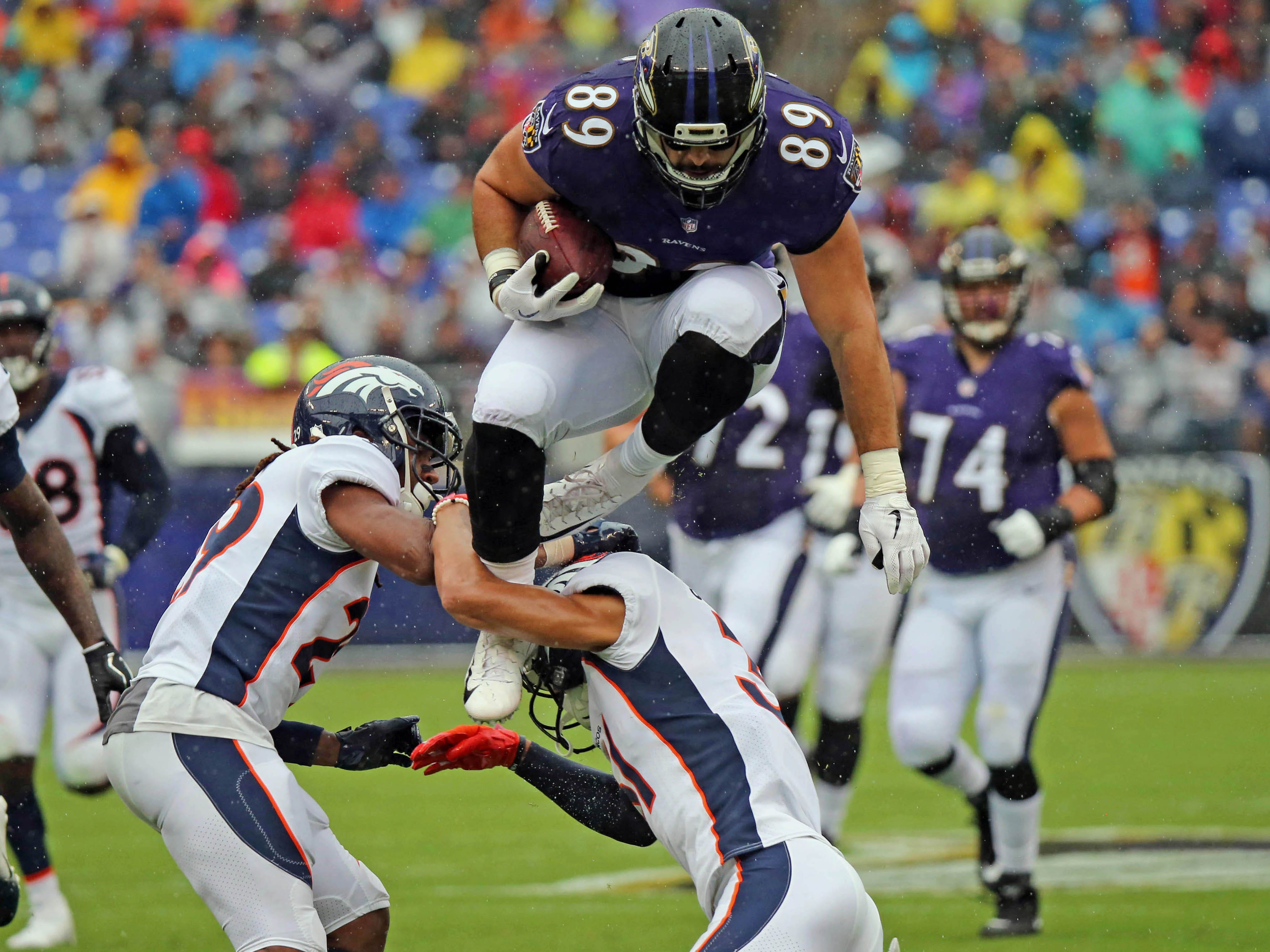 Baltimore Ravens tight end Mark Andrews leaps over Denver Broncos defenders following his catch at M&T Bank Stadium.