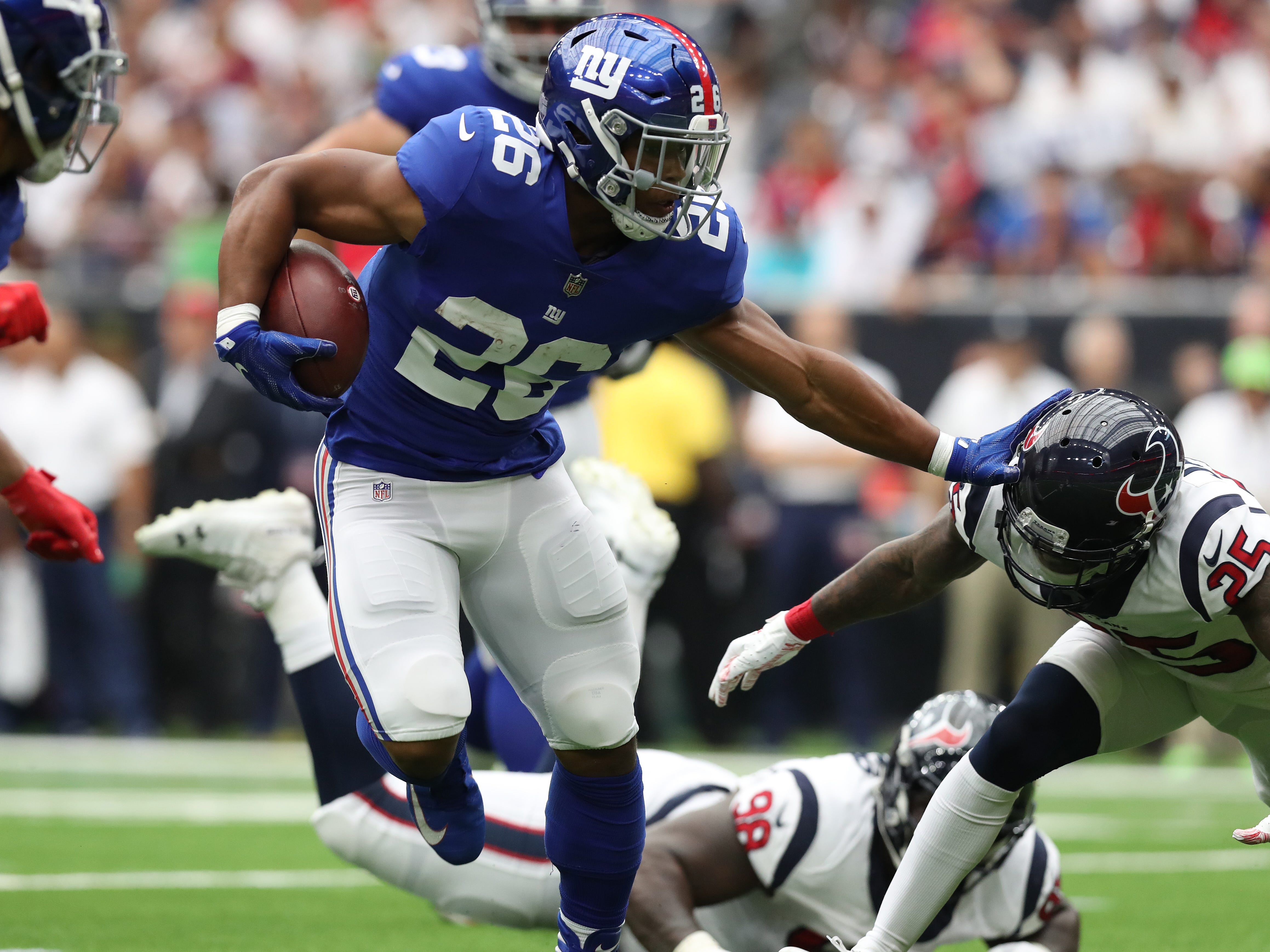 New York Giants running back Saquon Barkley runs with the ball for a first quarter touchdown against Houston Texans safety Kareem Jackson at NRG Stadium.