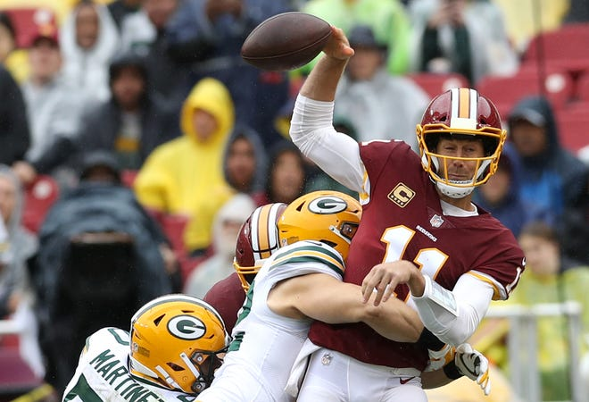 Clay Matthews #52 of the Green Bay Packers hits quarterback Alex Smith #11 of the Washington Redskins in the first half at FedExField on September 23, 2018 in Landover, Maryland.