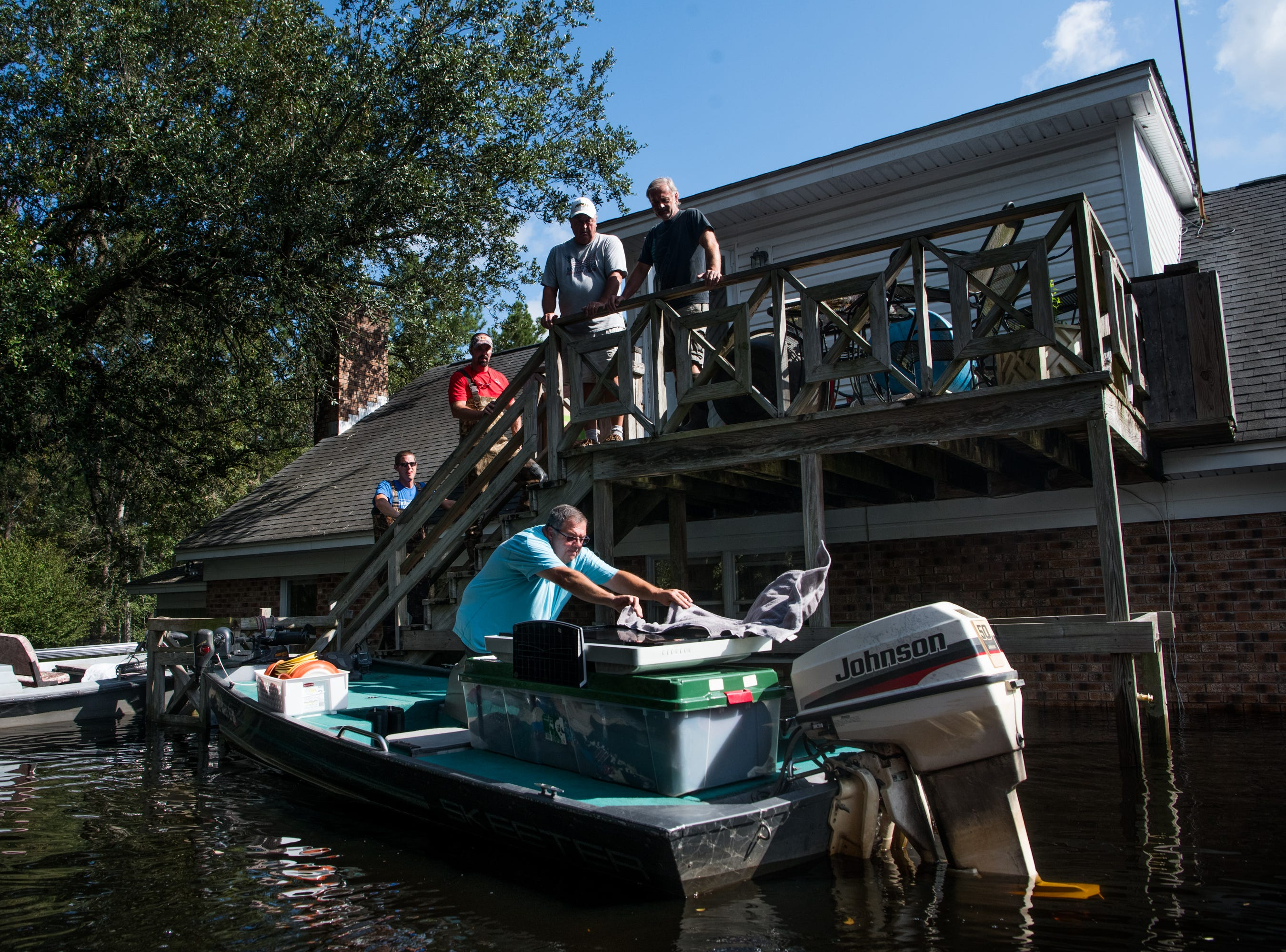 People use boats to rescue valuables from a home inundated by floodwaters caused by Hurricane Florence near the Waccamaw River on Sept. 23, 2018 in Conway, S.C.
