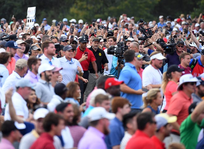 A sea of people follow Tiger Woods down the 18th green during the final round of the Tour Championship at East Lake Golf Club.