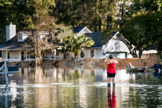 A woman documents  floodwaters caused by Hurricane Florence near the Waccamaw River on Sept. 23, 2018 in Conway, S.C. Floodwaters are expected to continue to rise in Conway over the next two days.