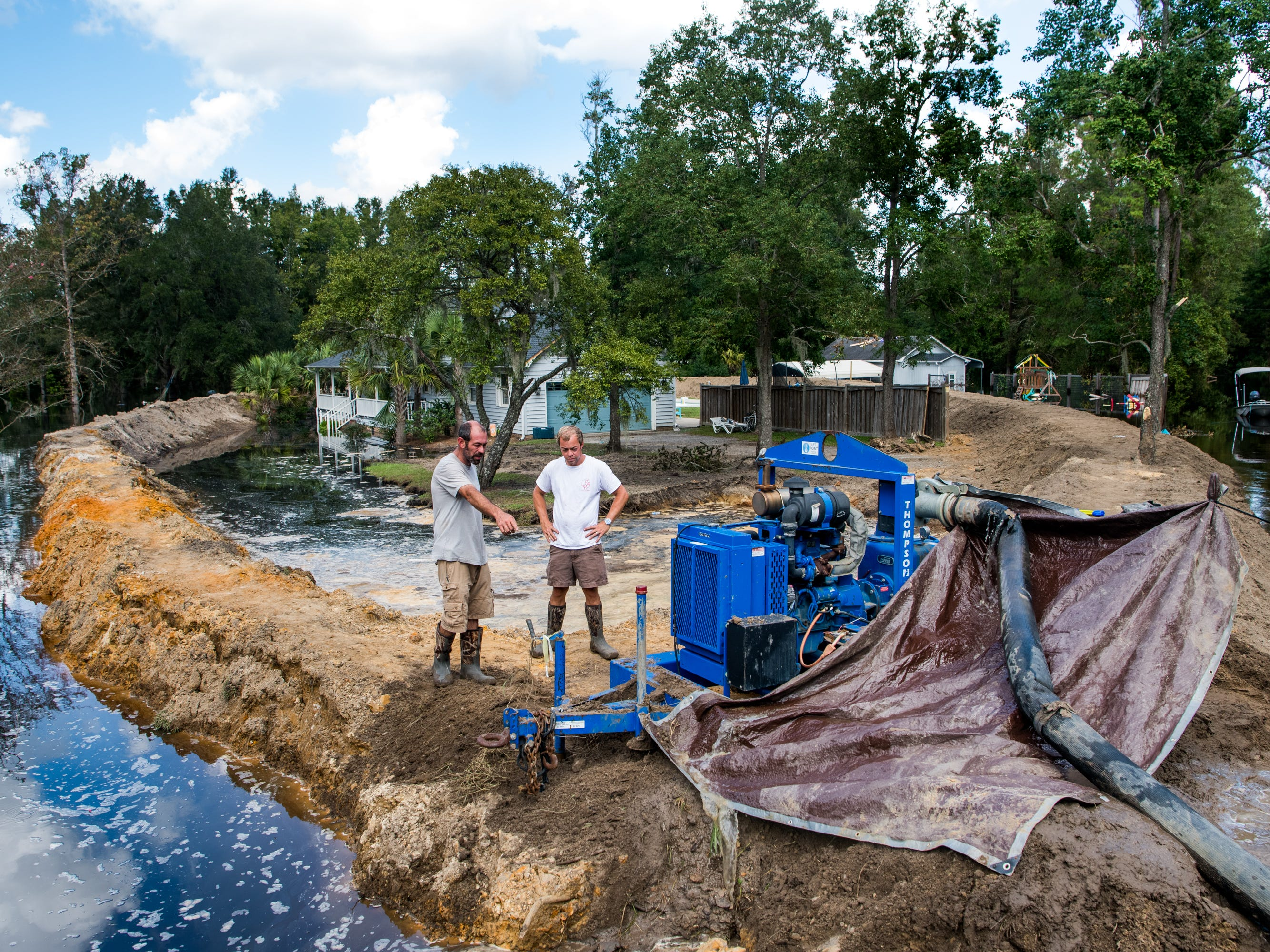 Jason Johnson, left, and homeowner Archie Sanders work to build a temporary levee to hold back floodwaters caused by Hurricane Florence near the Waccamaw River on Sept. 23, 2018 in Conway, S.C.