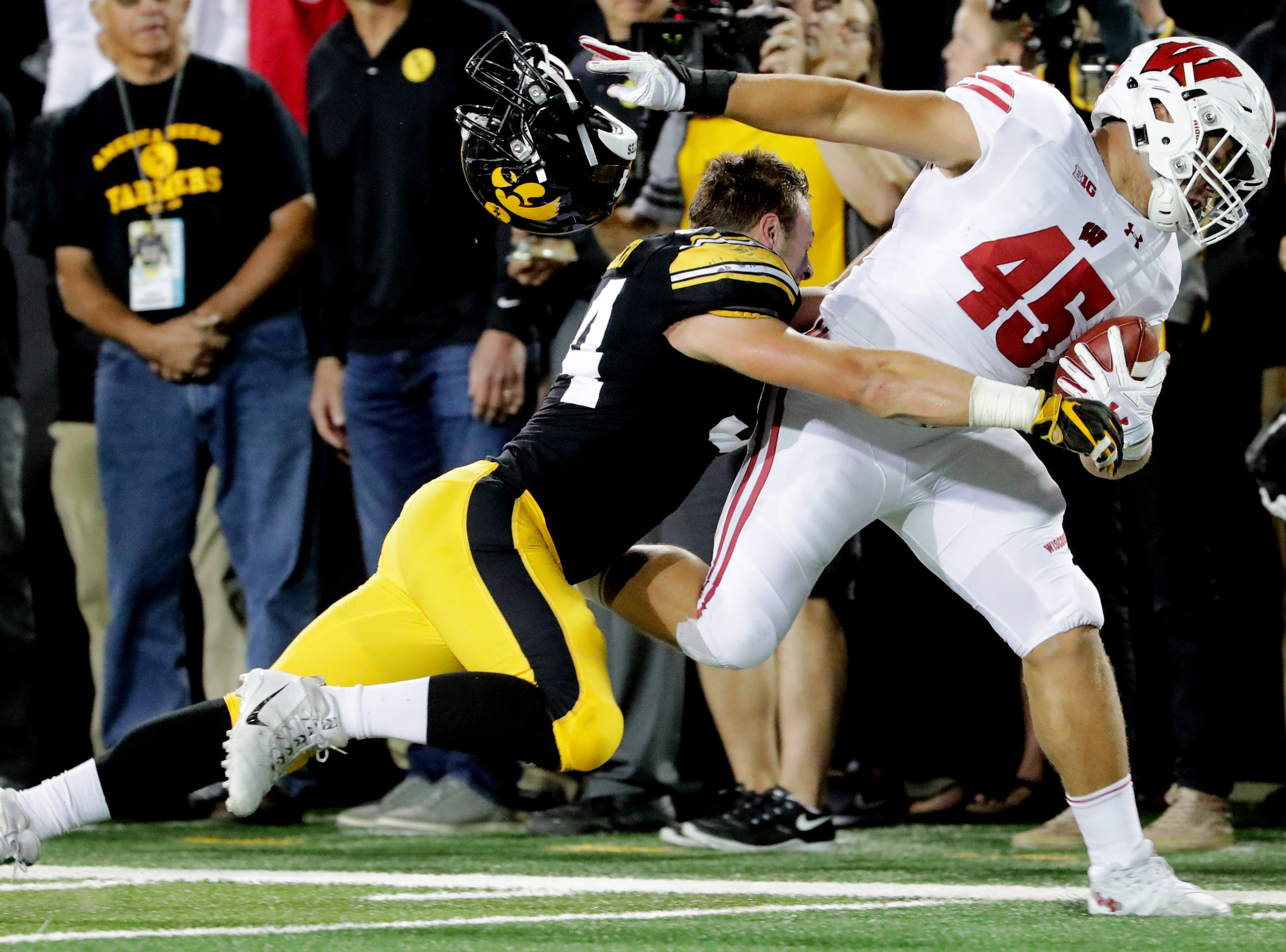 Wisconsin fullback Alec Ingold (45) picks up 33 yards on a run while stiff-arming Iowa linebacker Kristian Welch (34) during the second quarter  at Kinnick Stadium.