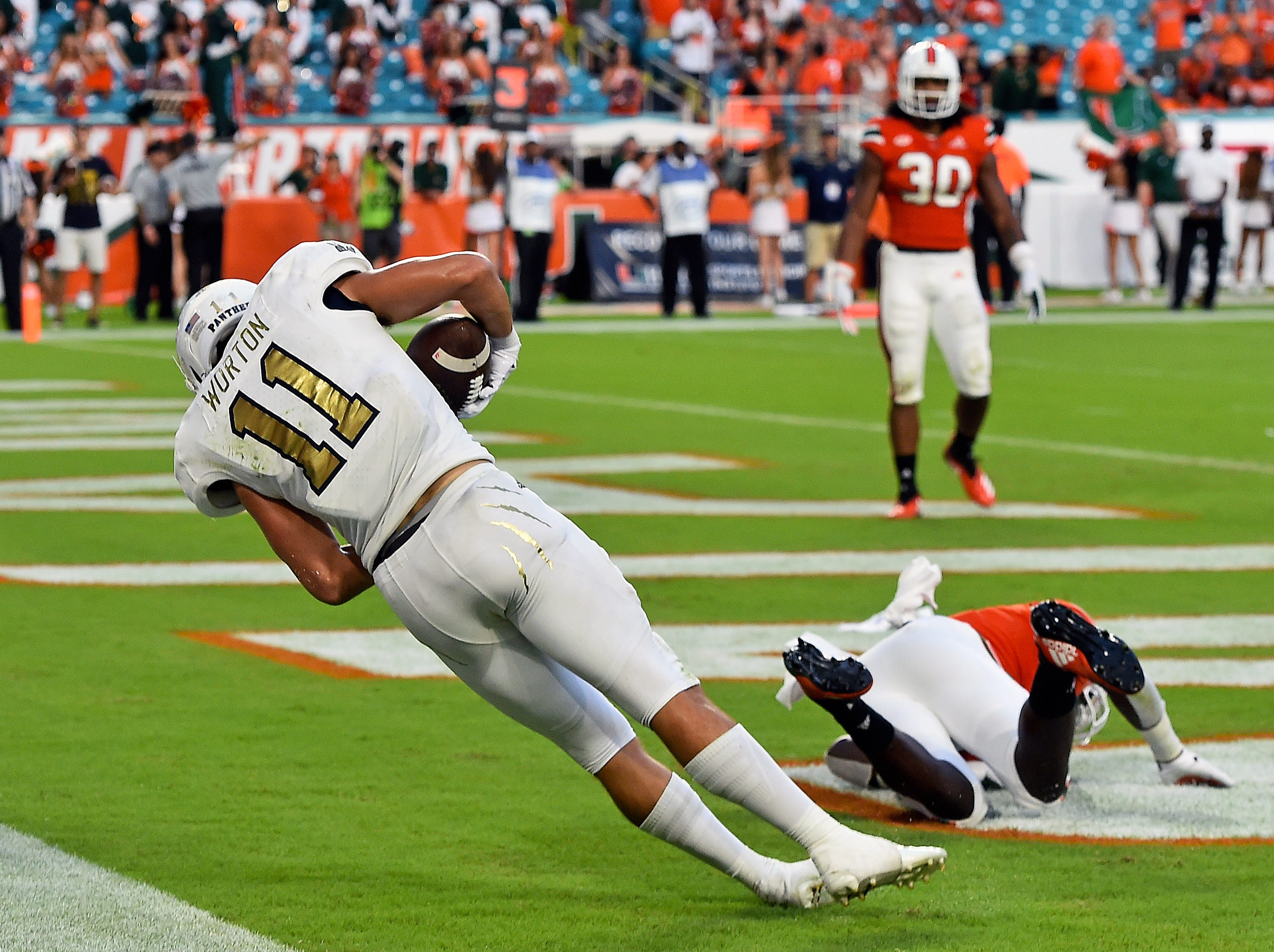 FIU Golden Panthers wide receiver CJ Worton (11) stays in bounds to score a touchdown against the Miami Hurricanes during the second half at Hard Rock Stadium.