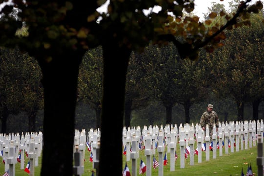 An American soldier walks among the graves of the Meuse-Argonne cemetery in northeastern France on Sept. 23, 2018.
