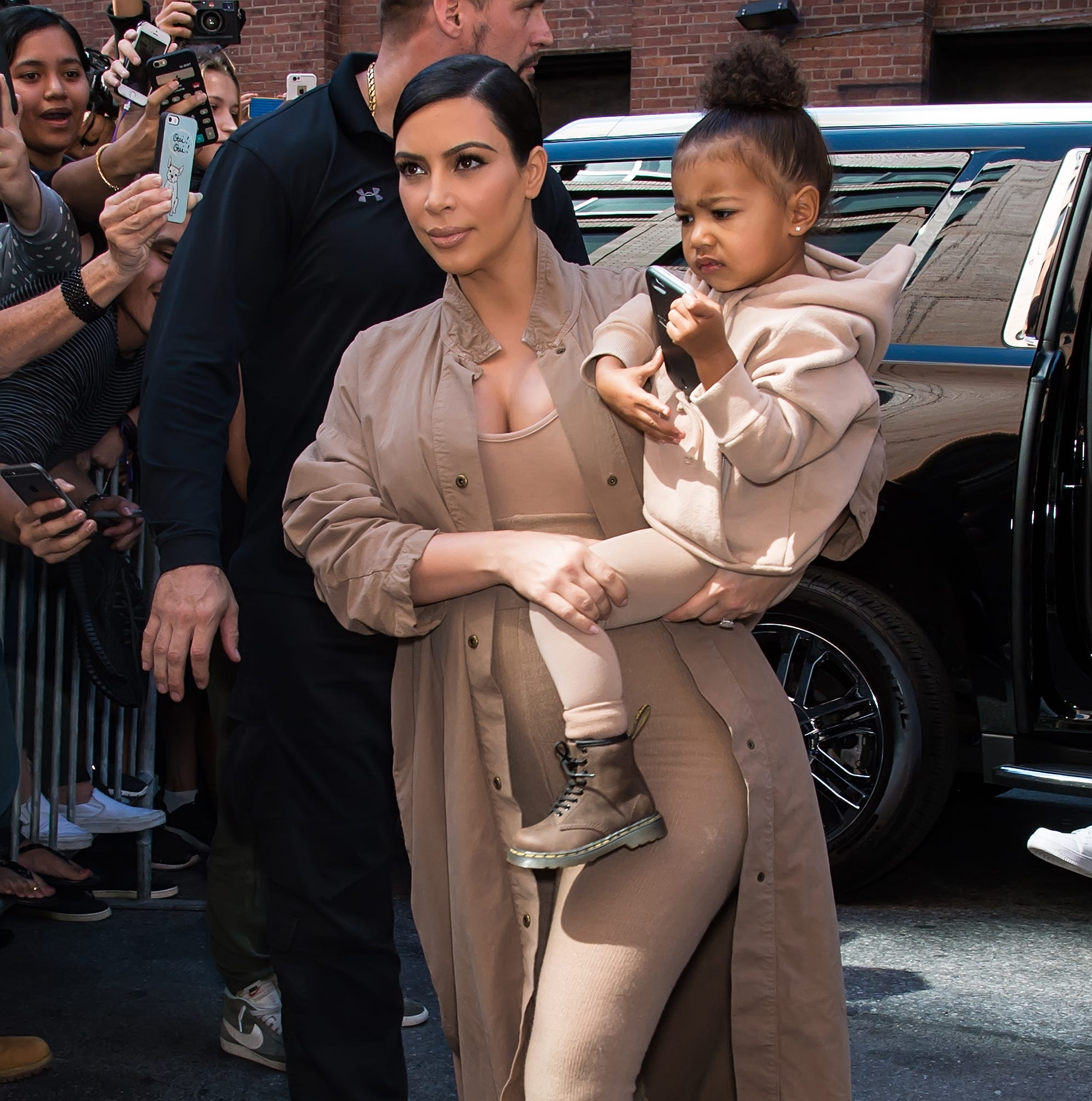 Kim Kardashian West and her daughter North West are seen arriving at Kanye West Yeezy Season 2 during Spring 2016 New York Fashion Week at Skylight Modern on September 16, 2015 in New York City.