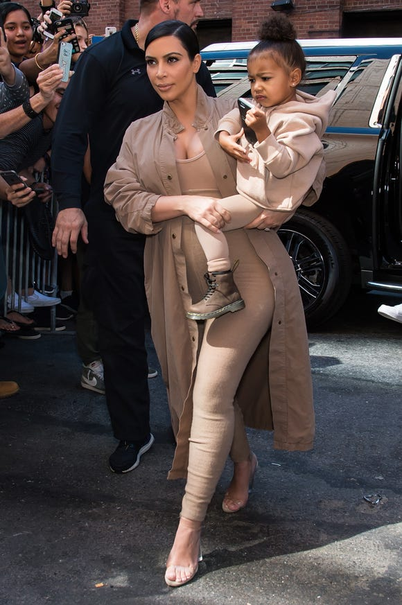 Kim Kardashian West and daughter North in 2015, arriving at Kanye West Yeezy Season 2 during Spring 2016 New York Fashion Week in New York City.